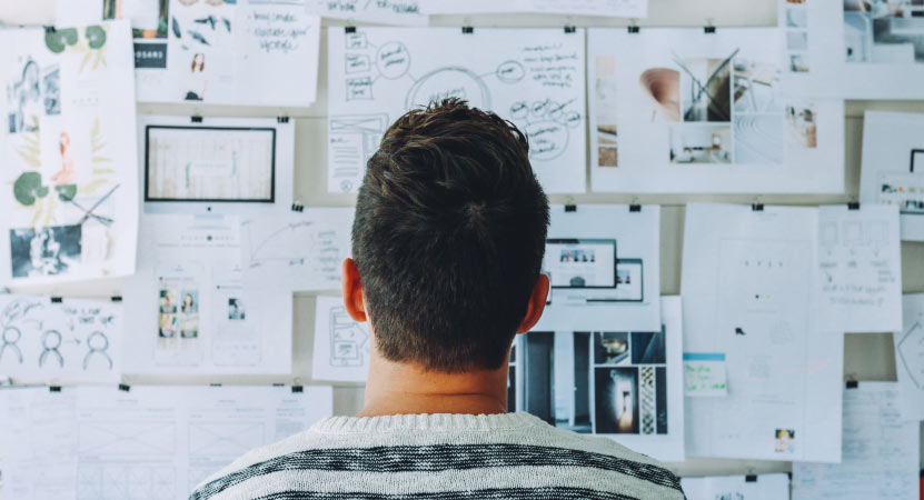 man looking at whiteboard of papers to assist in content creation